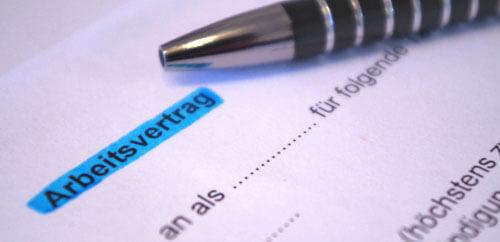 Große Ansicht eines Arbeitsvertrag mit Kugelschreiber als Grundlage für Fragen zum Arbeitsrecht